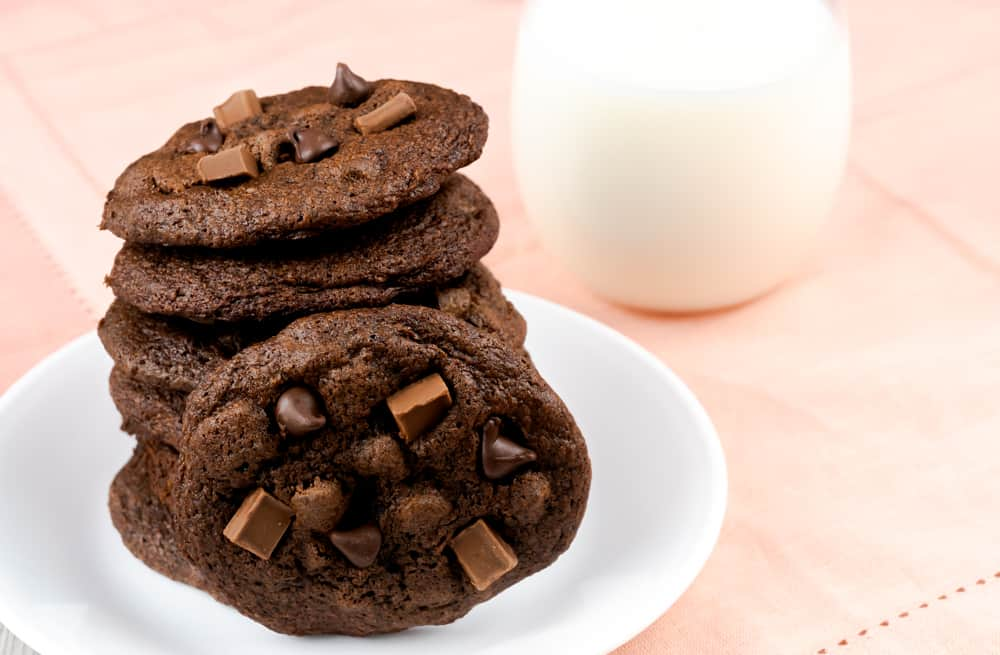 A plate of stacked chocolate cookies with chocolate chips and chunks with a glass of milk.