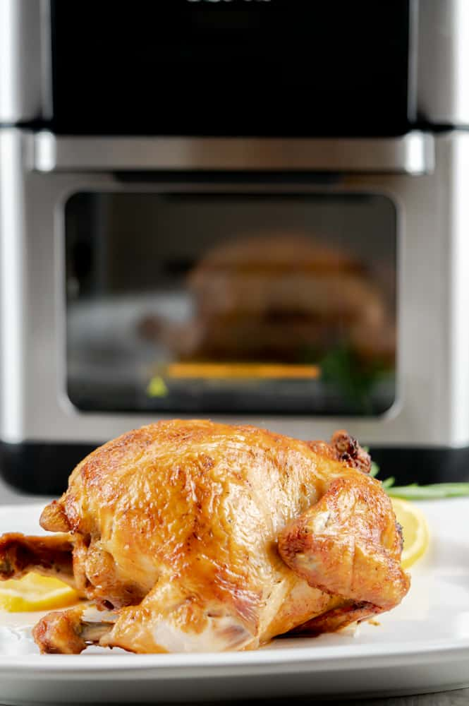 Faux rotisserie chicken on a serving plate in front of the Instant Pot Vortex.
