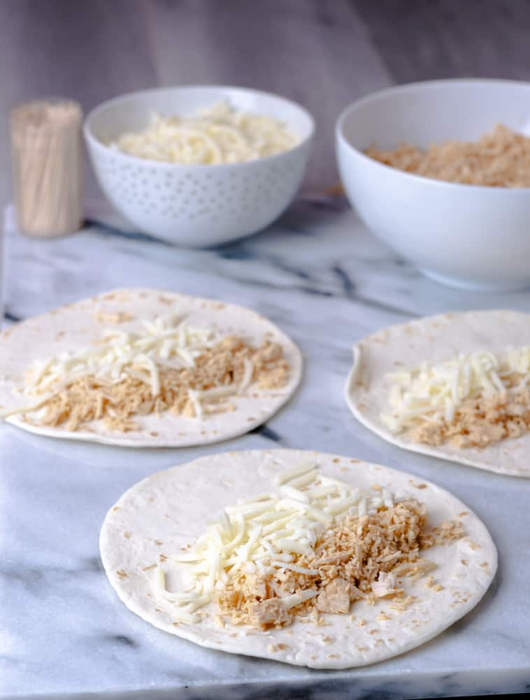Prep station of tortillas, shredded chicken, and cheese.