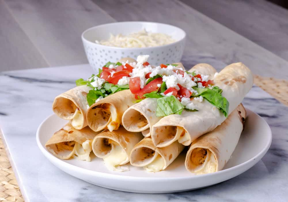 A plate with chicken and cheese taquitos garnished with diced tomatoes, chopped lettuce, and crumbled cheese.