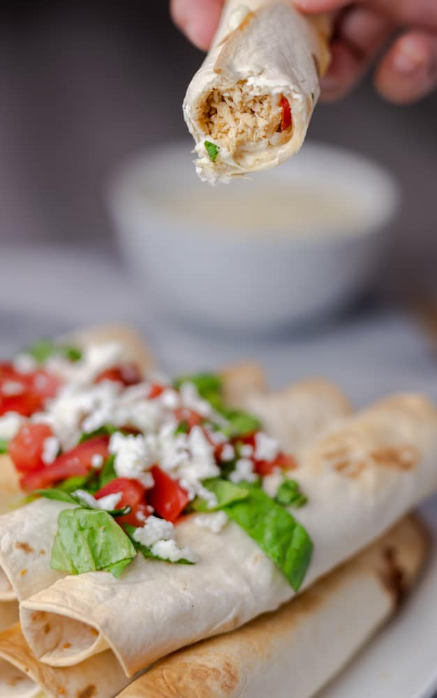Air fryer chicken and cheese taquitos garnished with lettuce, tomatoes, and cheese.