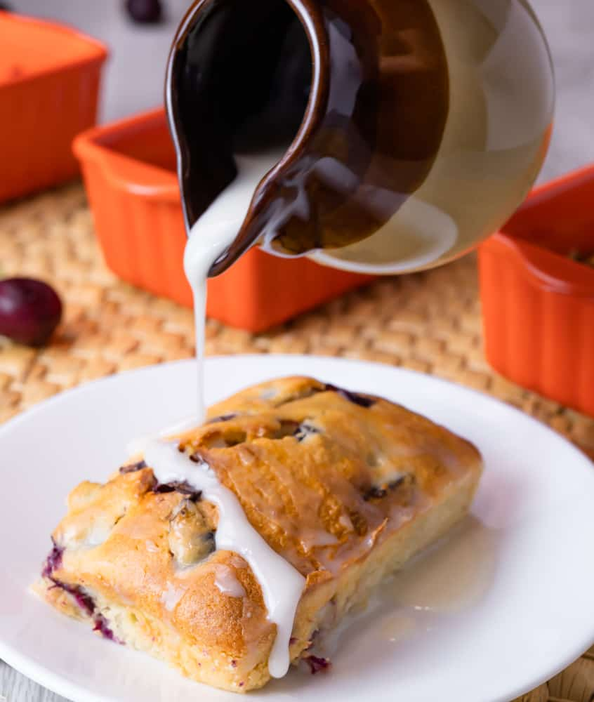 Mini loaf cherry cake on white plate being drizzled with a brown pitcher of sweet glaze.