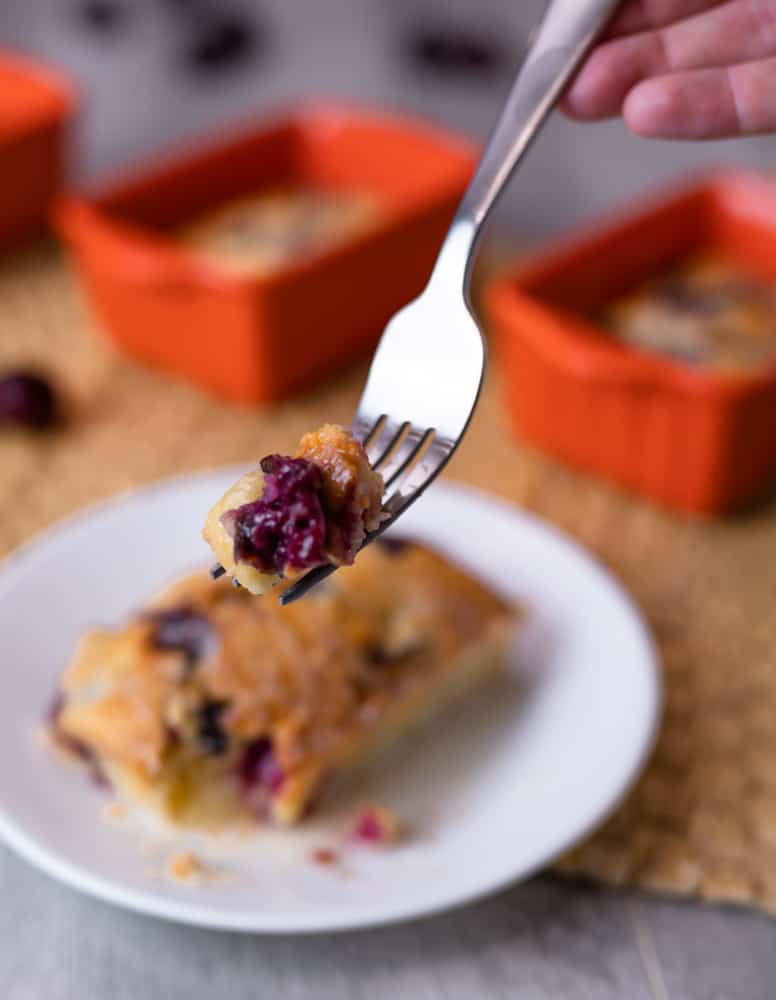 A fork with a piece of mini cherry loaf rising above a plate of cherry cake.