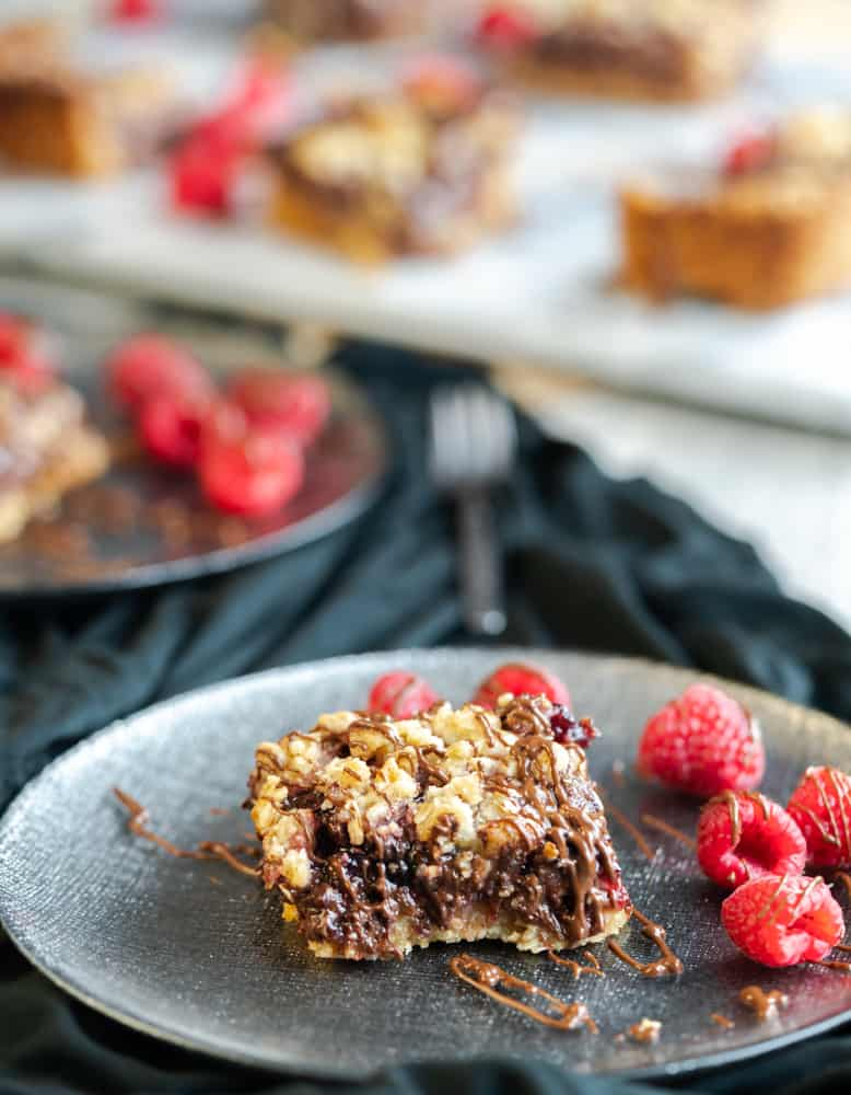 These chocolate raspberry crumble squares have a crunchy oatmeal bottom and then layered with raspberry jam, semi-sweet chocolate chips. Topping off these delicious squares is an oatmeal streusel topping and drizzled chocolate.