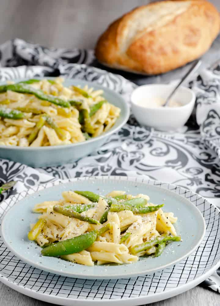 Penne pasta made in the Instant Pot and tossed in olive oil and served with fresh sugar snap peas and asparagus then garnished with Parmesan cheese.