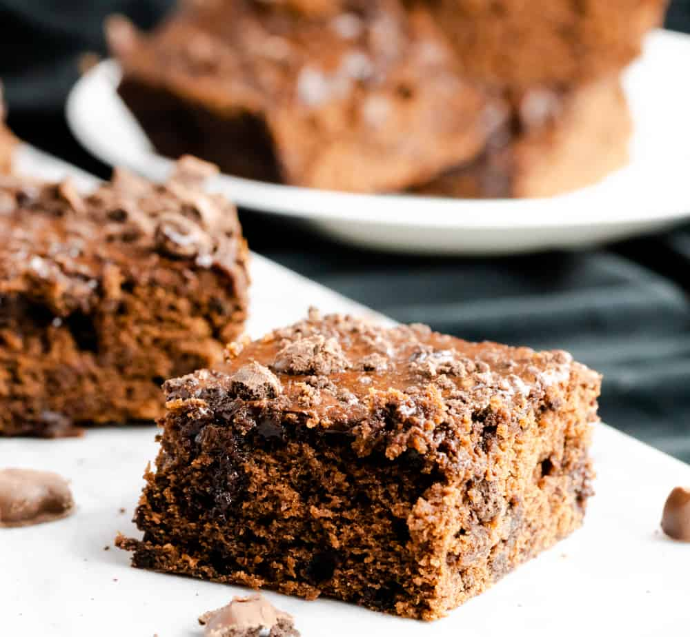 These chewy chocolate brownies are made with crushed mint cookies. They are frosted with a chocolate glaze and garnished with crushed cookies.