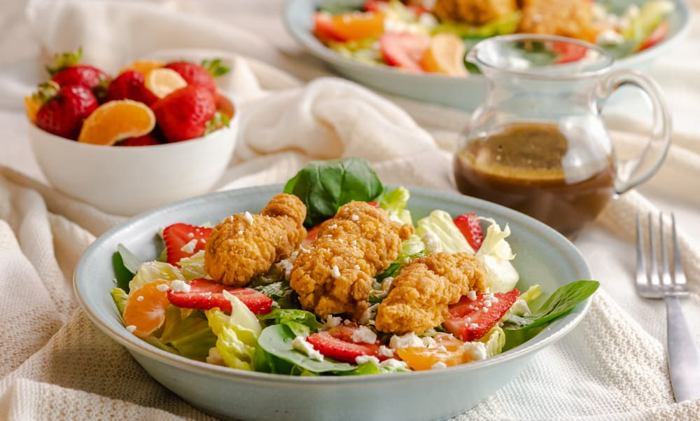Crispy chicken salad in a bowl with fresh fruit behind the bowl with a side of vinaigrette.