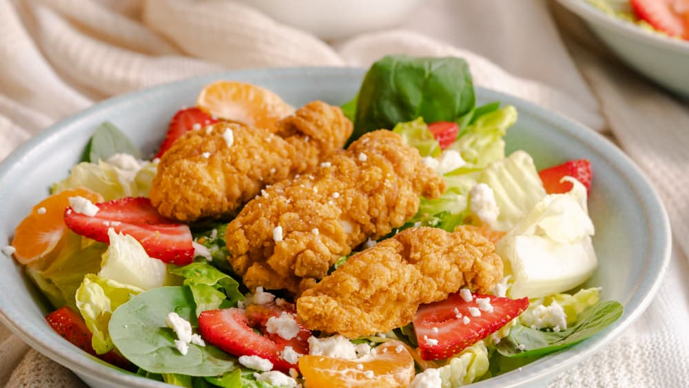 Three chicken strips sitting on bed of romaine lettuce, sliced strawberries, and oranges.