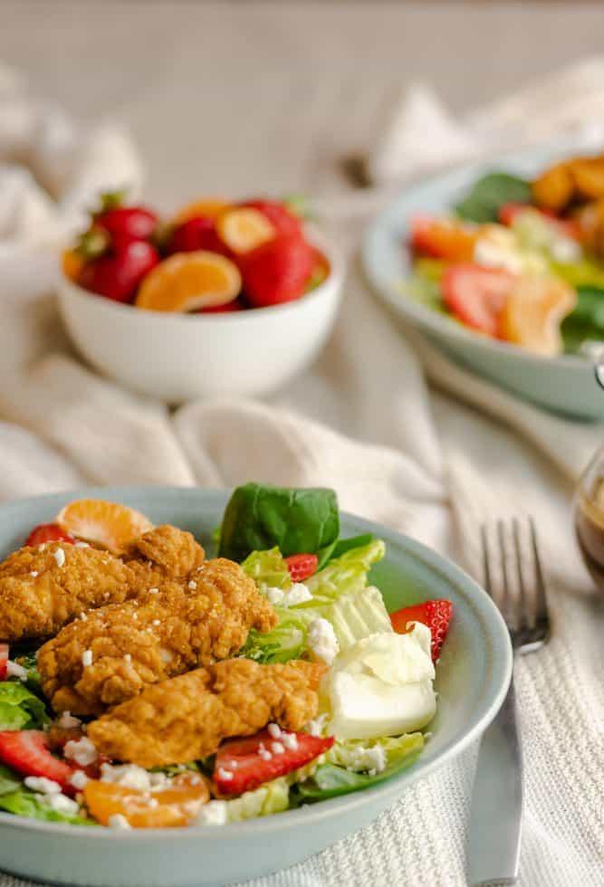 Strawberry & Orange crispy chicken salad served in a blue bowl.