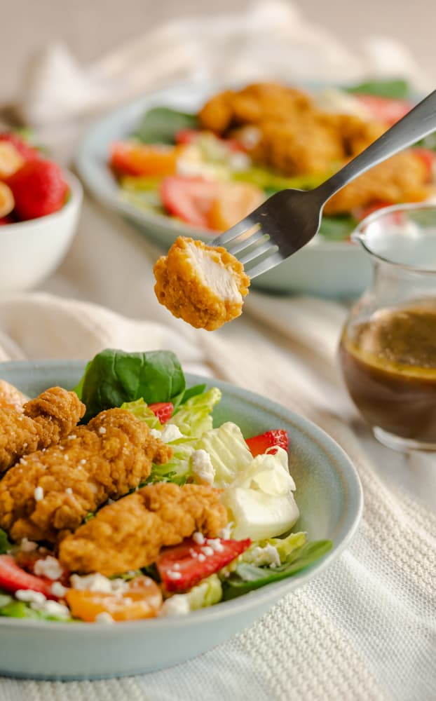 A fork of cut chicken strip over a bowl of salad.