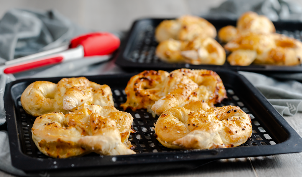 Air fryer rack with four garlic mozzarella pretzels.