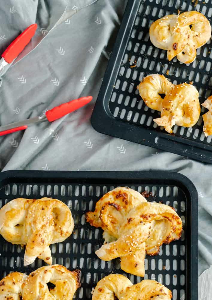 Air fryer pretzels resting on air fryer racks with tongs beside the racks.