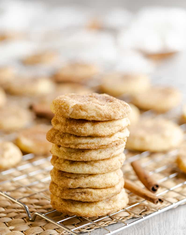 A stack of snickerdoodle cookies on wire rack with cookies blurred in the background.