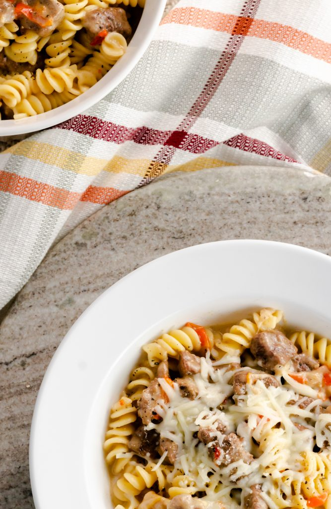 Spiral pasta with pieces of beef, julienned peppers, and onions, and garnished with cheese.
