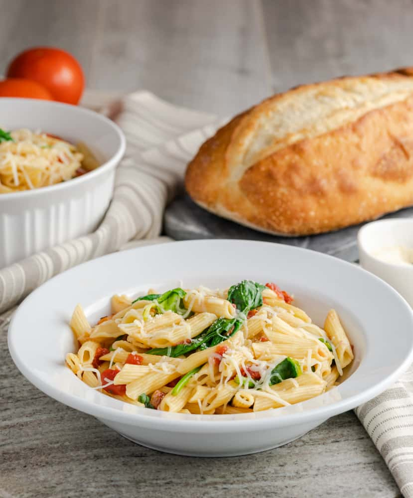 Penne pasta with spinach and tomatoes served with an Italian loaf of bread.