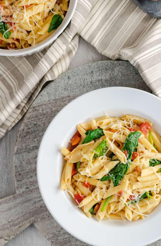 Four ingredients Instant Pot tomato and spinach penne pasta served in a white-rimmed bowl and garnished with cheese.