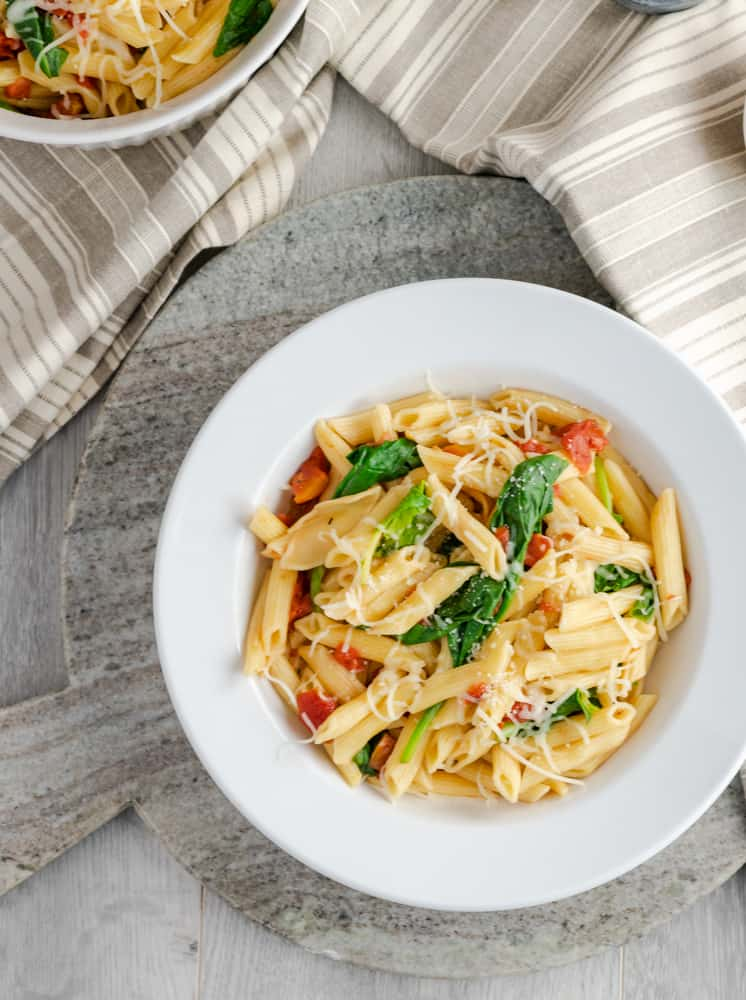 Tomato and spinach penne pasta in white-rimmed bowl sitting on marble platter.