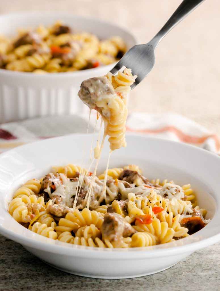 A fork on rotini pasta with beef and stringy cheese.