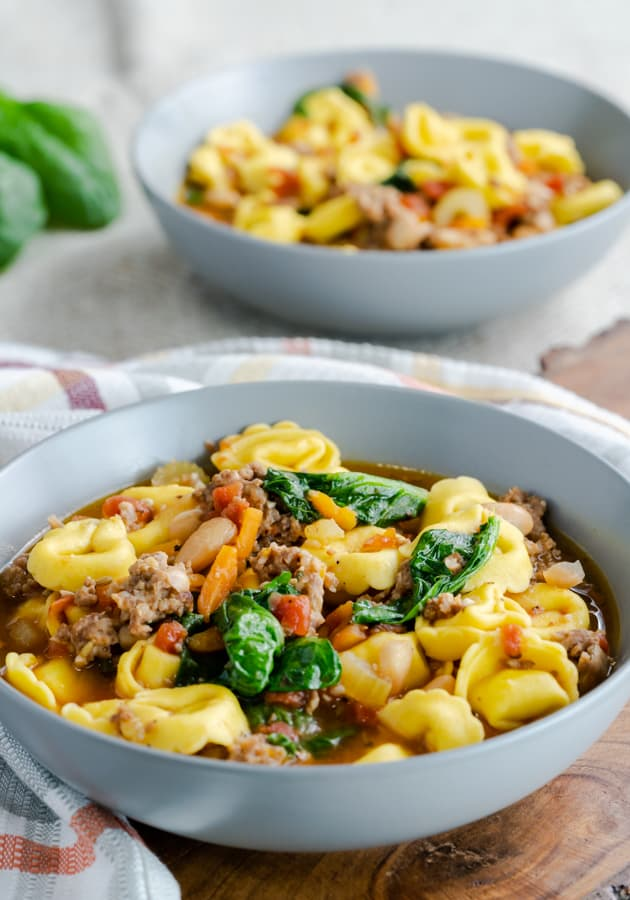 Instant Pot Sausage & Tortellini Soup in a gray bowl topped with cooked spinach.