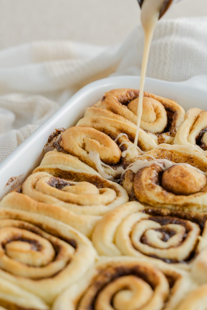 Drizzled mocha cappuccino cinnamon rolls on a white plate and a white dish filled with cinnamon rolls.