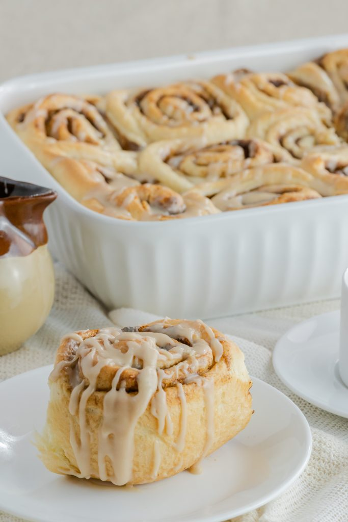Mocha cappuccino cinnamon rolls on a white plate and a white dish filled with cinnamon rolls.