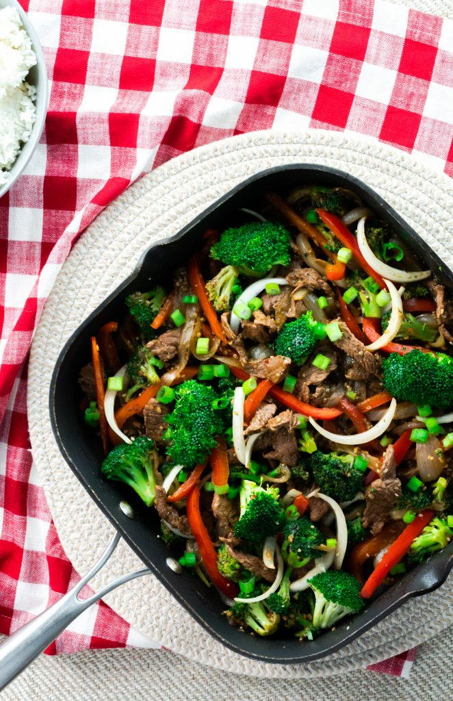 Easy and flavorful beef stir fry made with beef sirloin, julienned peppers, sliced onions, and broccoli florets in a square skillet.