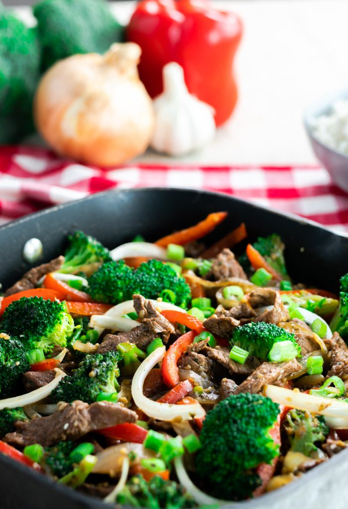 Beef stir fry with julienned red peppers and onion tossed with broccoli and scallions in square skillet.
