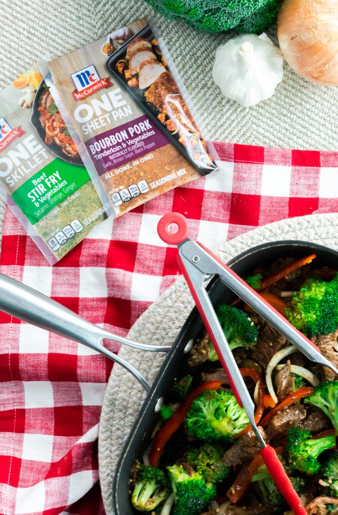 Square skillet of beef stir fry with red tongs beside two seasoning packets.