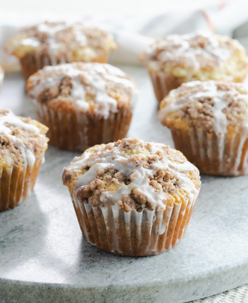 Close up of sour cream coffee cake muffin with sweet glaze on gray circular board.