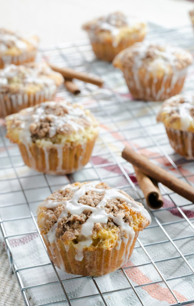 Sour cream coffee cake muffins resting on wire rack and drizzled with glaze.