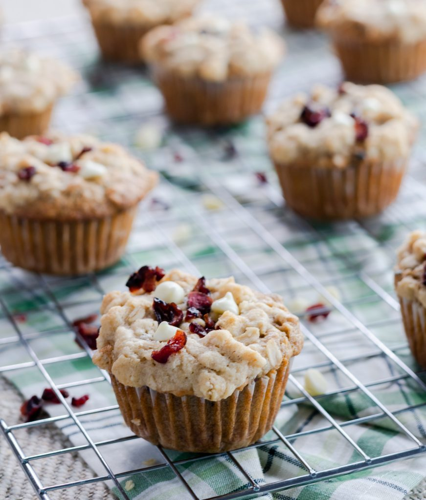 Cranberry Orange Oatmeal Muffins topped with an oatmeal streusel, dried cranberries, and white chocolate chips.