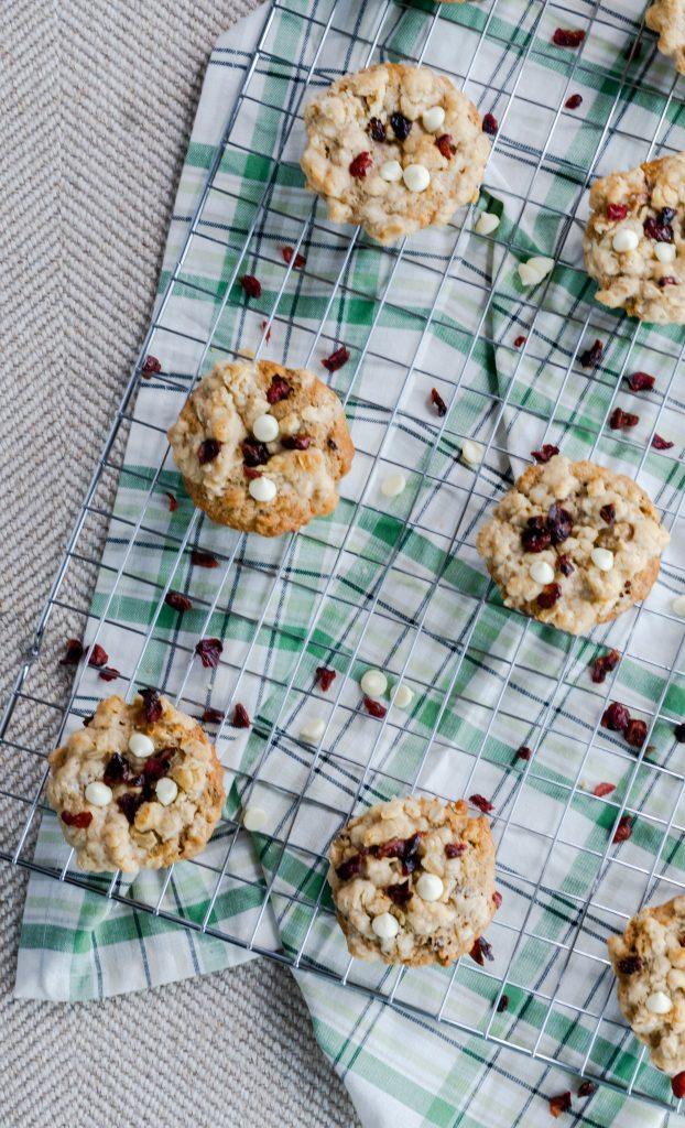 Top view of Cranberry Orange Oatmeal Muffins topped with an oatmeal streusel, dried cranberries, and white chocolate chips on wire rack.