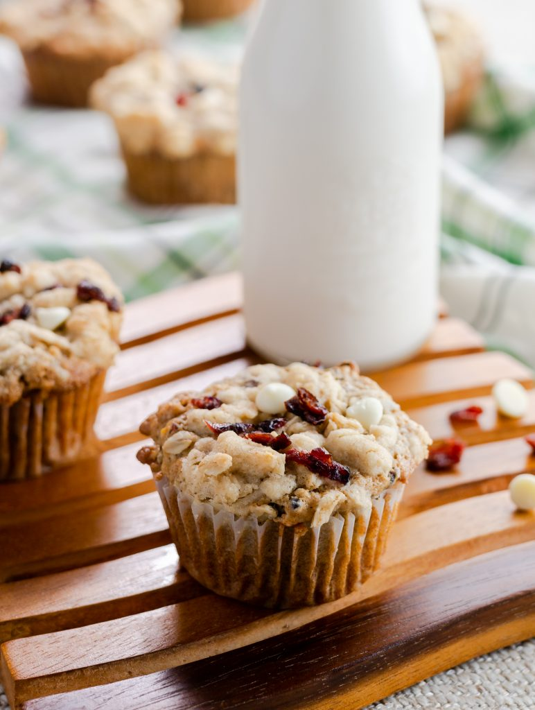 Cranberry Orange Oatmeal Muffin sitting on wooden serving board with a glass of milk in the background.