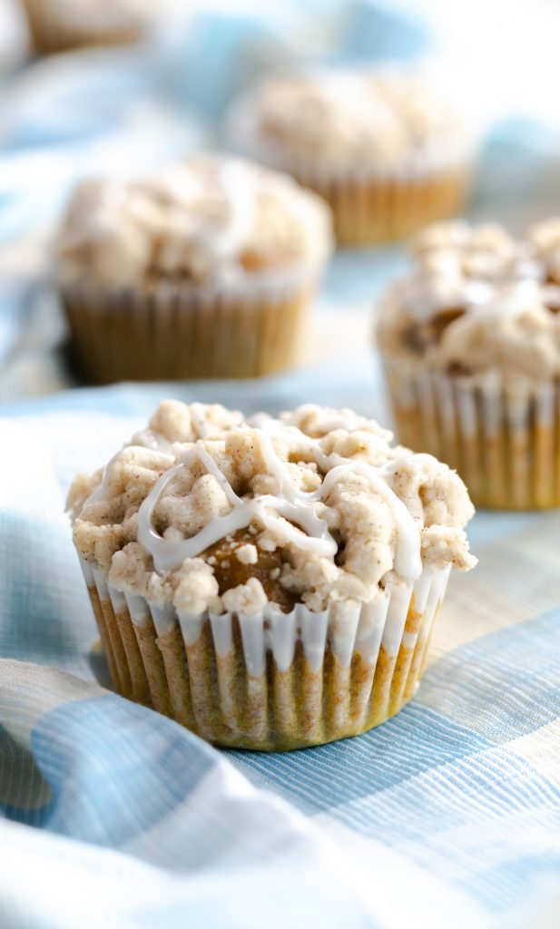 Muffins made with pumpkin, homemade pumpkin spice, and topped with a buttery streusel. Drizzled on these cupcakes is a spiced vanilla glaze.