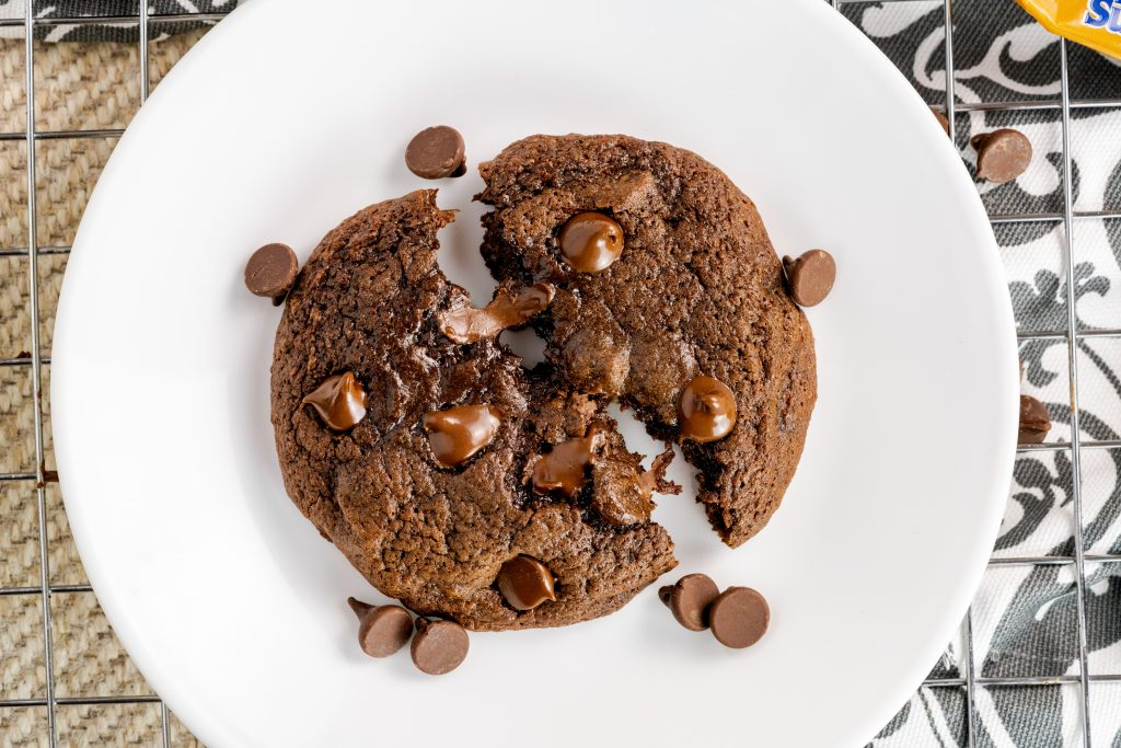 Made from scratch double chocolate fudge cookie topped with chocolate chips on white dessert plate.