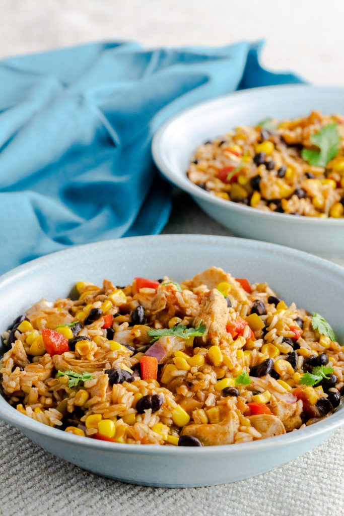 Two Bowls of chicken burrito bowls recipe with gray and blue background.