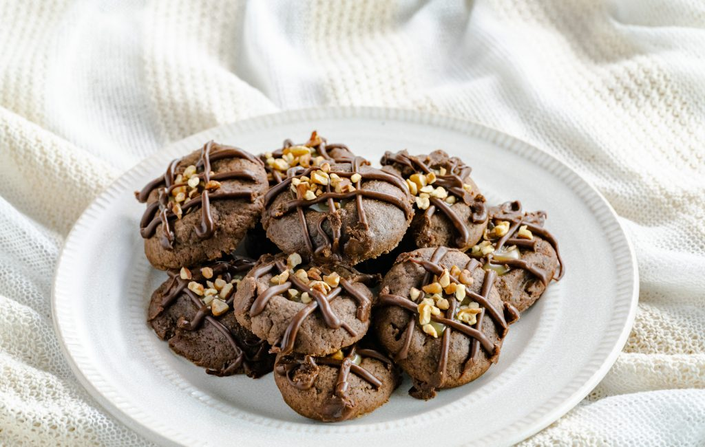 A plate of thumbprint cookies drizzled with chocolate and topped with chopped pecans.
