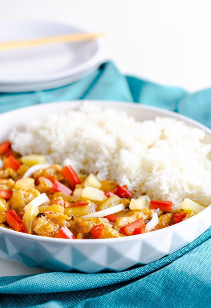 White bowl with sauced chicken, chopped peppers and onion, and a side of rice.