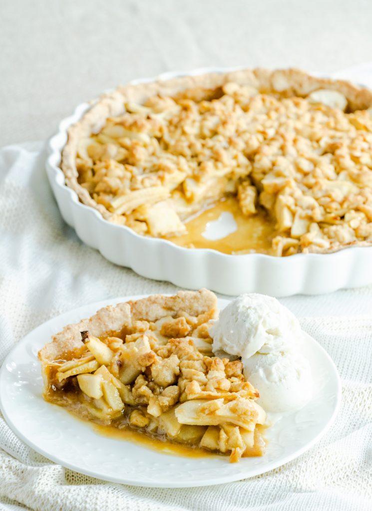 caramel apple pie with vanilla bean ice cream on white plate