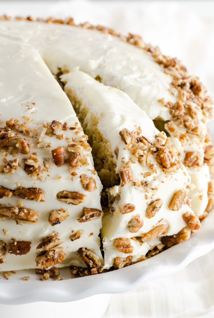 Butter Pecan Cake with a slice cut and decorated with toasted pecans.