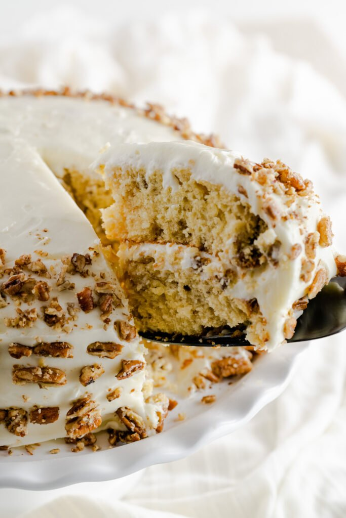 Slice of butter pecan cake with toasted pecans.