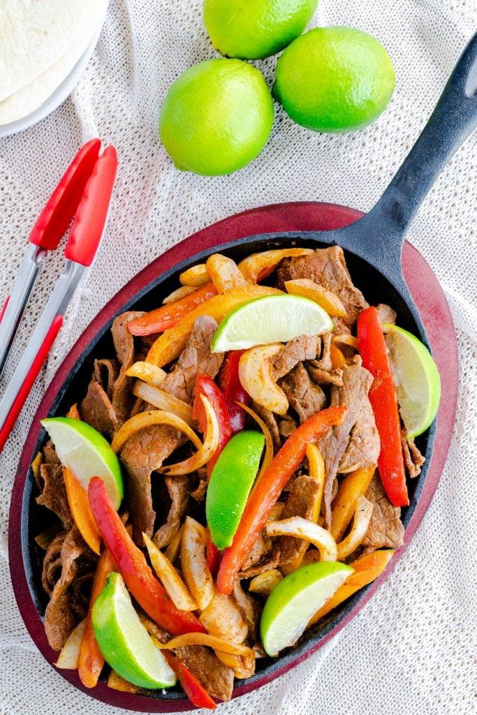 Steak fajitas in fajita skillet with red tongs and limes.