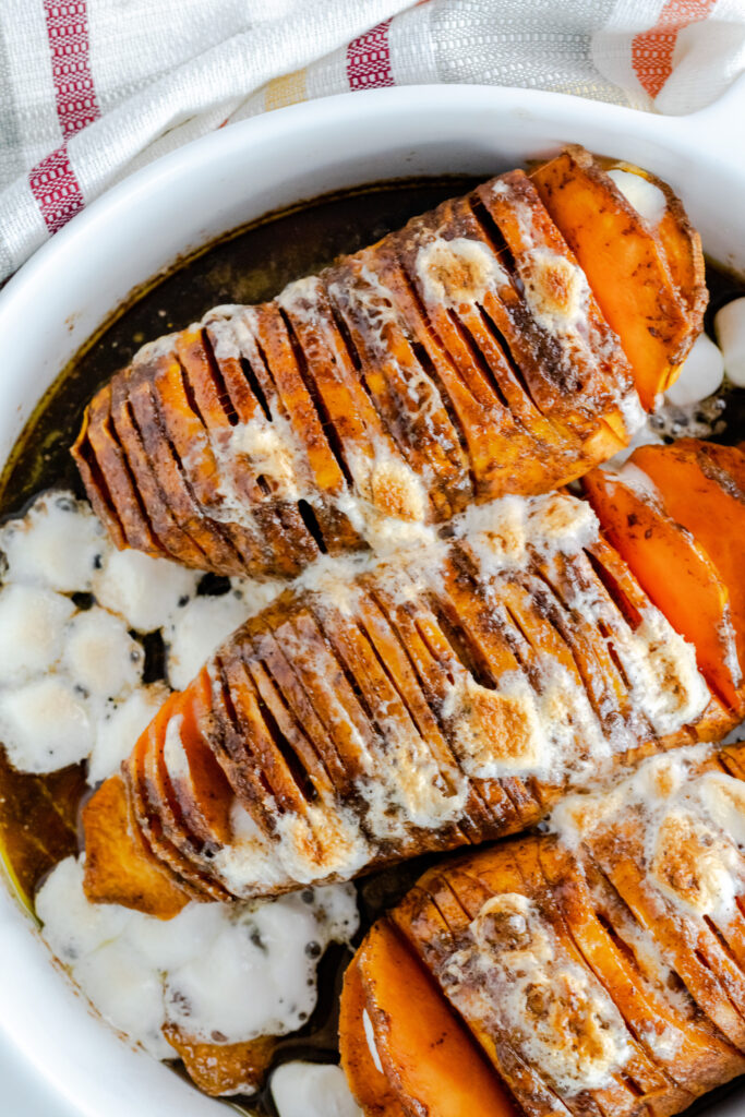 Hasselback sweet potato casserole with marshmallows in white baking dish.