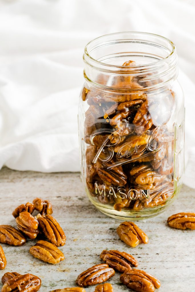 Toasted candied pecans with white background.