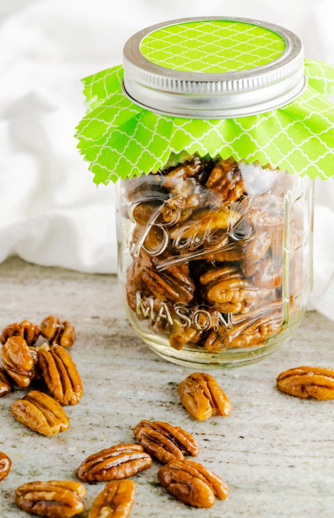 Jar with candied pecans with green fabric under the lid.