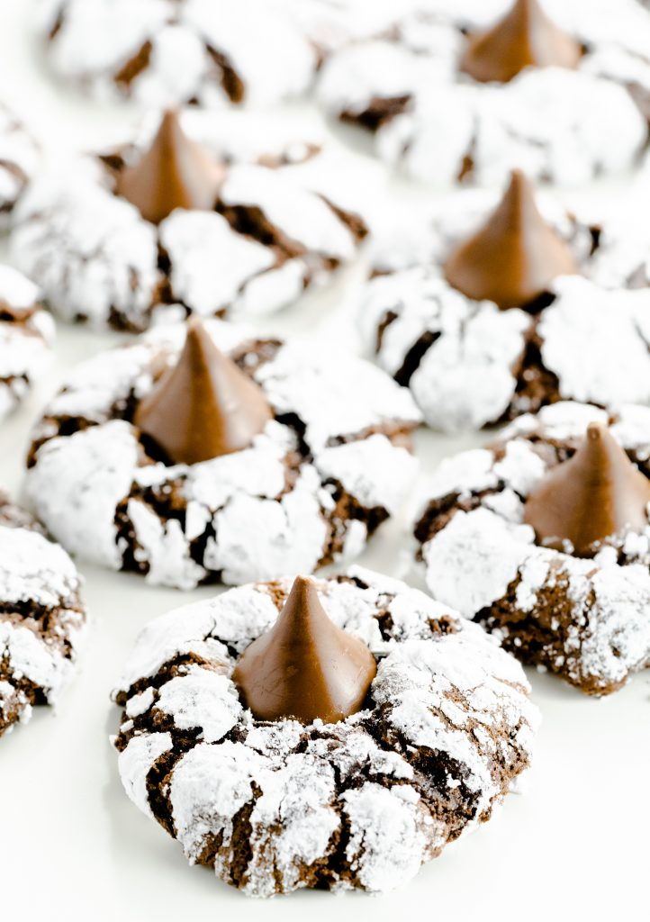 Chocolate cookies rolled into powdered sugar and topped with a pressed chocolate kiss in center.
