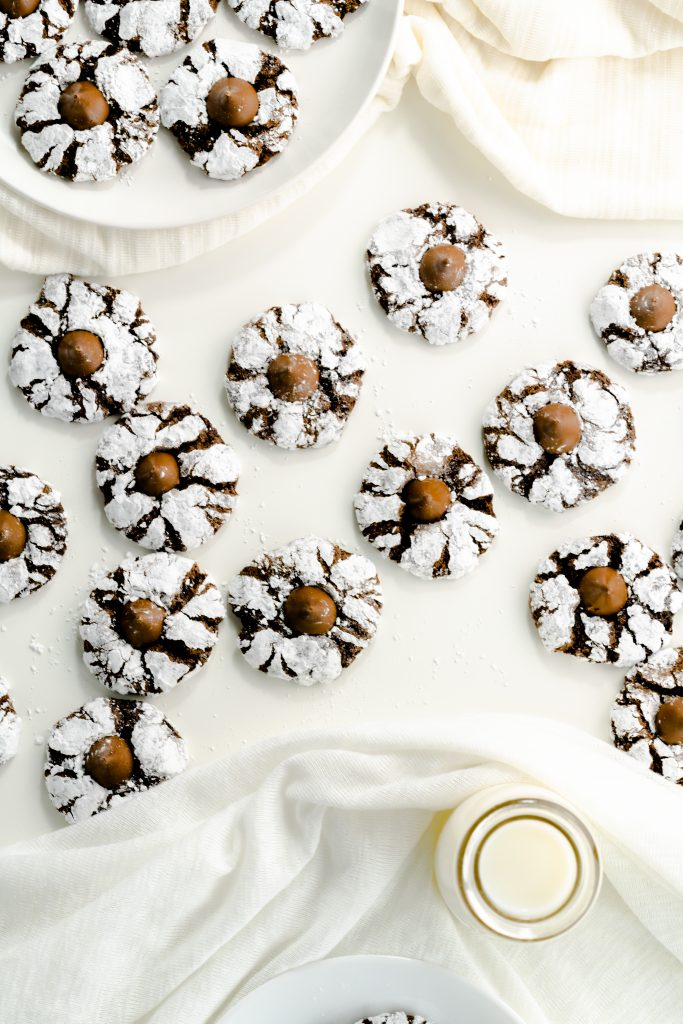 Scattered chocolate cookies with kisses on white background.