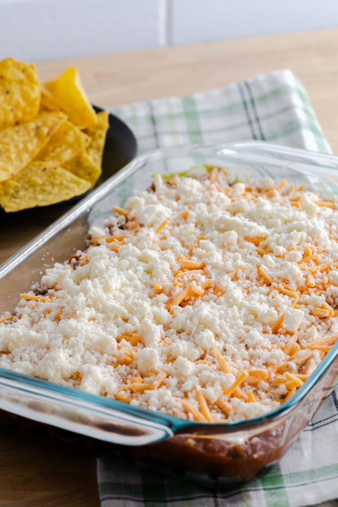 Crumbled cheese on top of no-bake layered dip with a plate of tortilla chips.