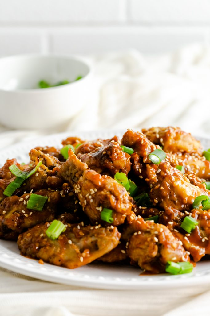 Platter of sweet and sticky chicken wings topped with toasted sesame seeds and scallions.