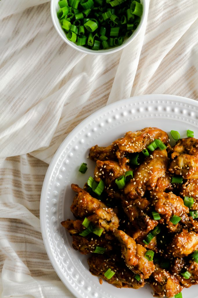 Saucy chicken wings garnished with sesame seeds and scallions.